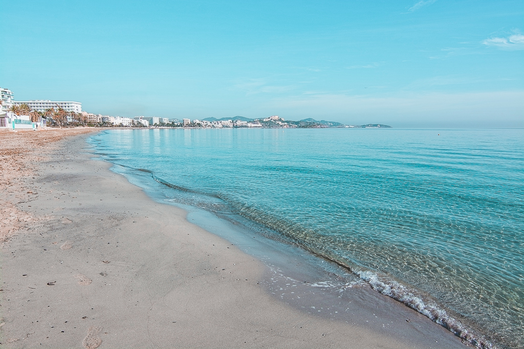 Empty beautiful sandy Playa d'en Bossa beach on a sunny and misty winter morning in December in Ibiza, Spain.